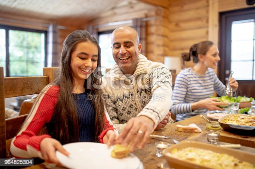A mid adult man serves his daughter dinner in a log cabin whilst his wife prepares to serve lettuce.