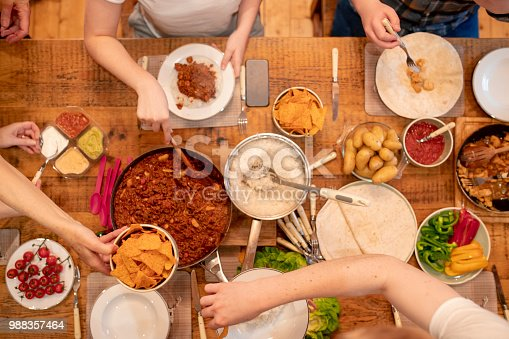 A group of friends serve dinner together in a log cabin whilst on a skiing holiday.