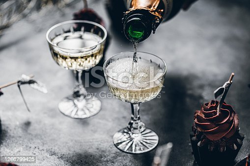 Close-up of pouring champagne in a glasses over black table with cup cake. Serving drinks for new years party.