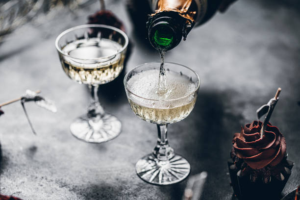 Serving drinks for new years party Close-up of pouring champagne in a glasses over black table with cup cake. Serving drinks for new years party. champagne stock pictures, royalty-free photos & images