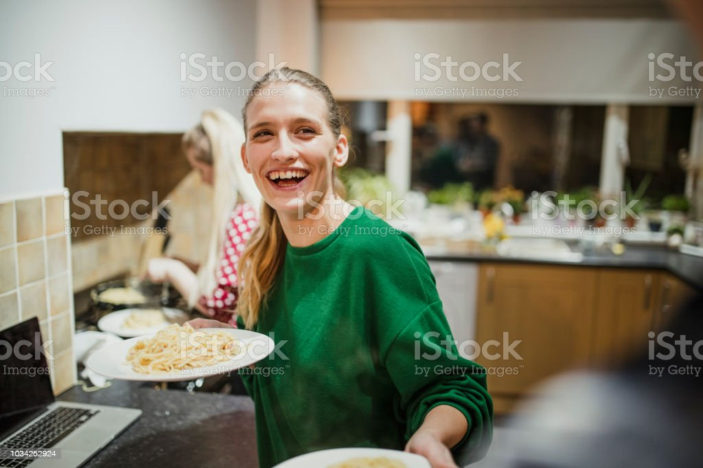 Young woman is serving spaghetti carbonara at her home dinner party.