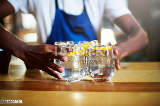 Serving Four Glasses of water with ice and lemon on a wooden counter by an African Ethnicity male Barista with a blue apron in Cape Town South Africa
