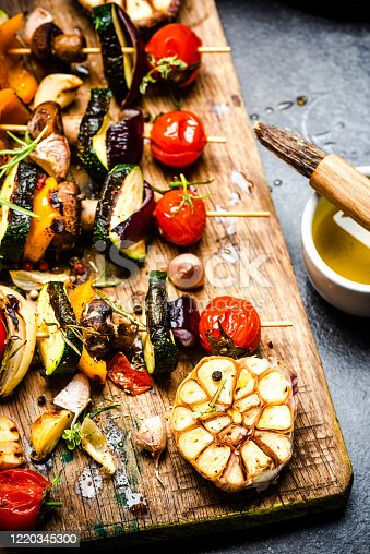 Serving Grilled BBQ Vegetables Skewers with Fresh Herbs, Marinate and Spices on Wooden Board . Summer Party Food