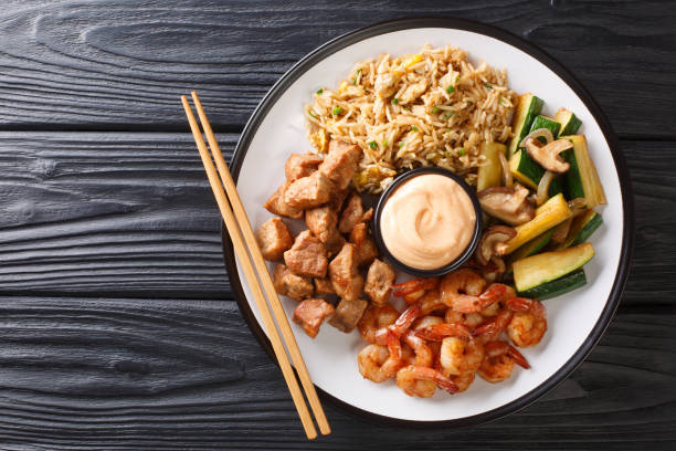 Serving hibachi of rice, shrimp, steak and vegetables served with sauce closeup in a plate. Horizontal top view stock photo