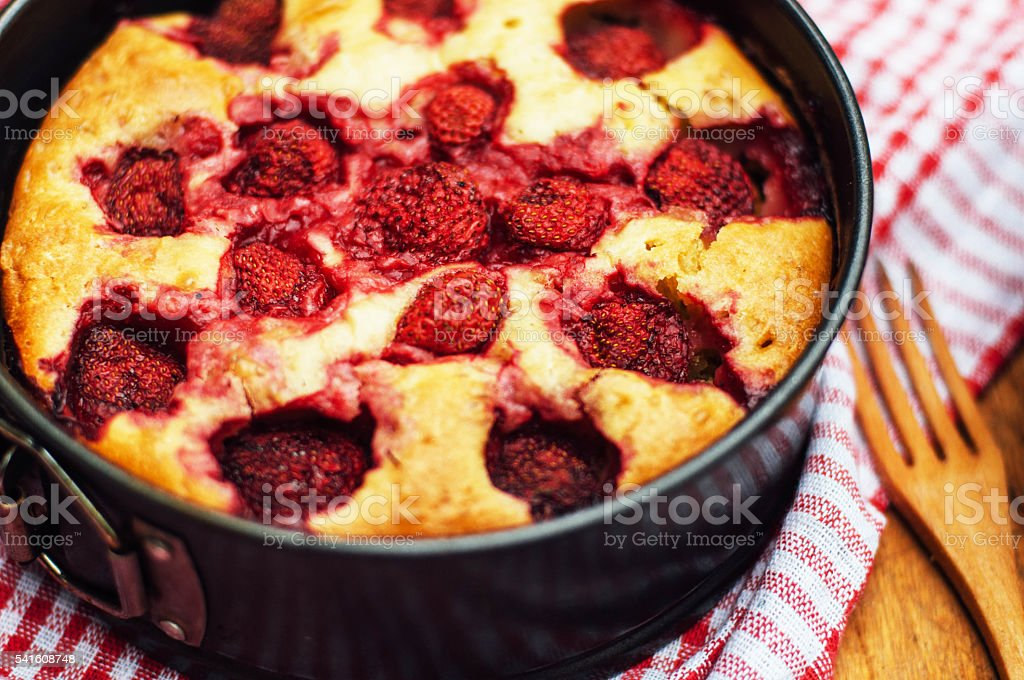 Serving homemade strawberry cake or pie on wooden rustic stock photo