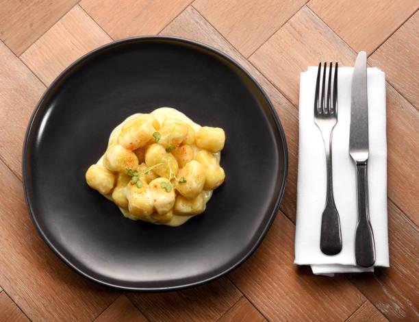 portion hausgemachte italienische gnocchi mit safran - safransauce stock-fotos und bilder