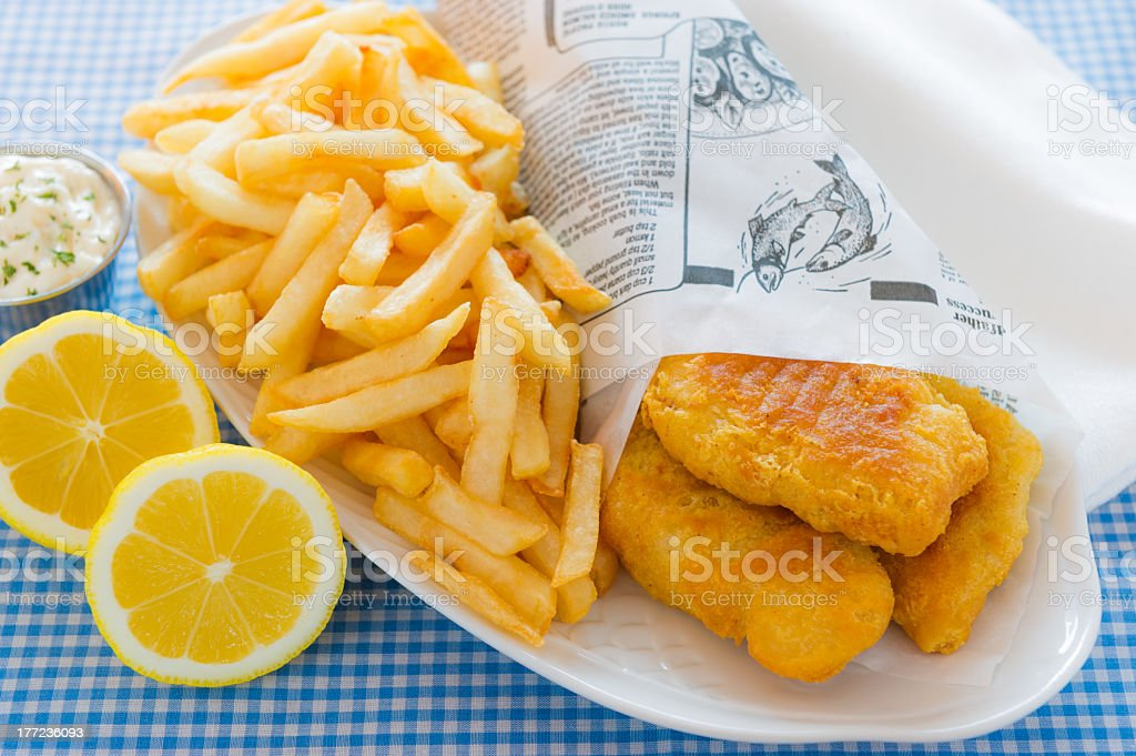 Serving of fish and chips served with lemon stock photo