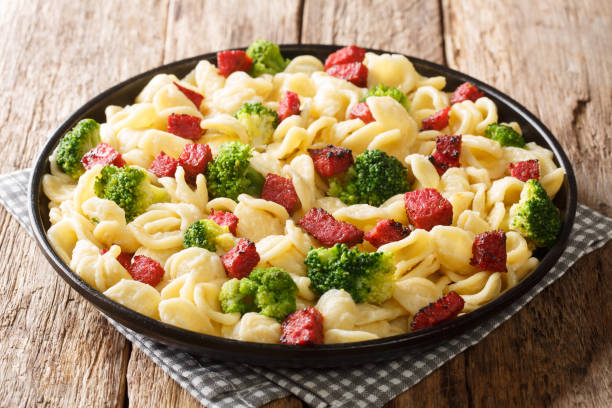 Serving of orecchiette pasta with broccoli and fried Italian sausages close-up in a plate. horizontal Serving of orecchiette pasta with broccoli and fried Italian sausages close-up in a plate on the table. horizontal orecchiette stock pictures, royalty-free photos & images