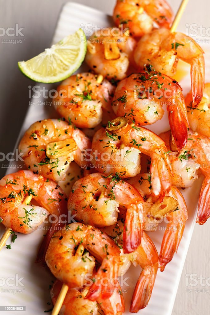 A serving of shrimp brochettes with a slice of lemon stock photo