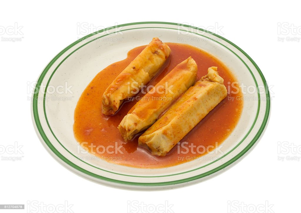 Serving of tamales in chili sauce on plate stock photo