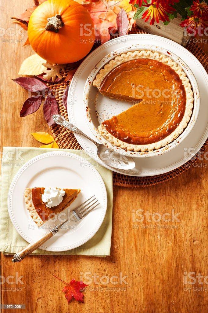 Serving of Thanksgiving Pumpkin Pie in Autumn Setting stock photo