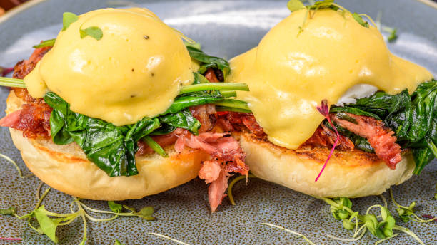 A serving of two Eggs Benedict, with a muffin base, ham, poached Eggs and hollandaise sauce stock photo