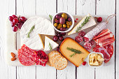istock Serving platter of assorted meats, cheeses and appetizers, top view on white wood 1186420751