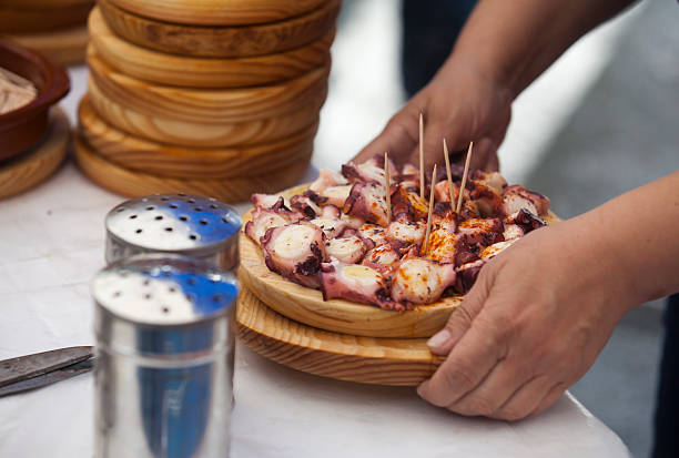 Serving Pulpo in Galicia Preparing and serving the famous dish Pulpo in Galicia galicia stock pictures, royalty-free photos & images
