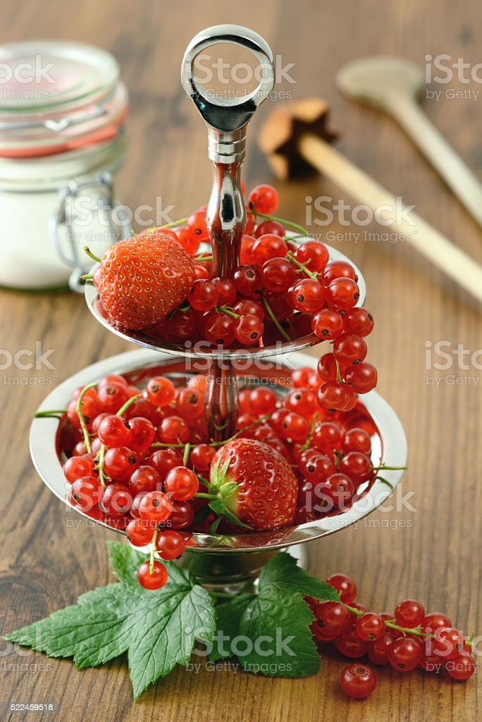 serving red currant and strawberries on metal plate. stock photo