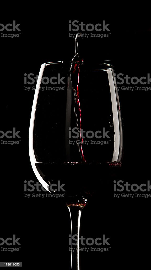 Serving red wine on a glass. Studio shoot, black background. royalty-free stock photo