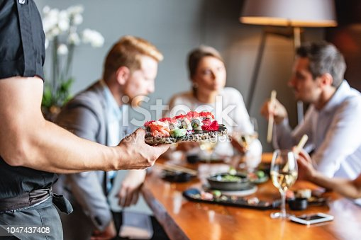 Waiter serving sushi plate at business lunch