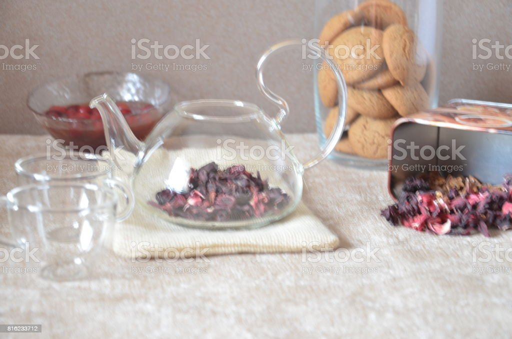 Serving table for breakfast, red tea in teapot. tea leaves, hibiscus and two glass cups for tea stock photo