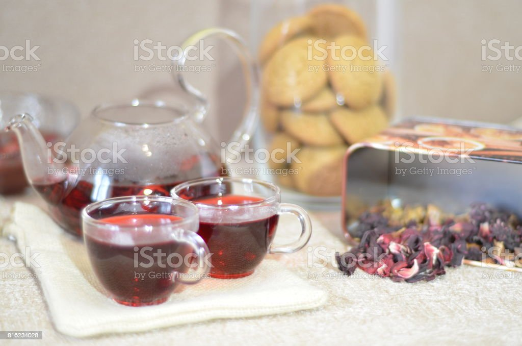 Serving table for breakfast, red tea in teapot. tea leaves, hibiscus and two glass cups with red tea stock photo
