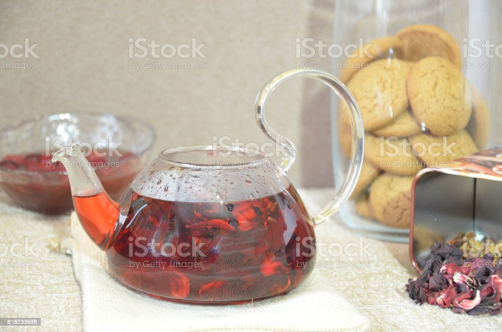 Serving table for breakfast, red tea in teapot. tea leaves, hibiscus stock photo