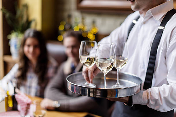 Serving wine Waiter serving white wine in restaurant waiter stock pictures, royalty-free photos & images