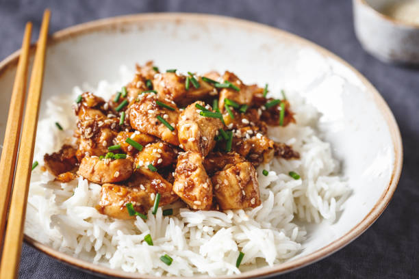 sesame chicken pieces with rice on a ceramic plate. chinese traditional dish. - miele dolci foto e immagini stock