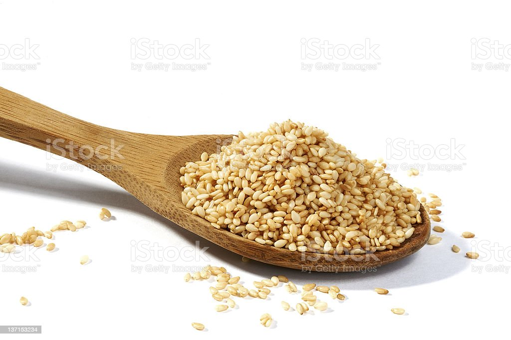 Sesame grains in large wooden spoon stock photo