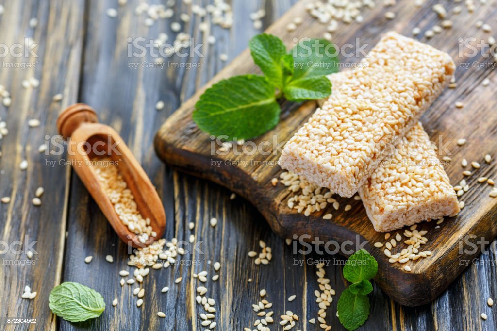 Sesame honey bars and wooden scoop. stock photo
