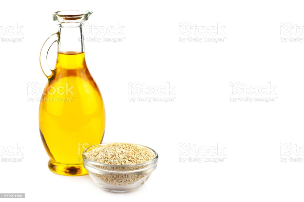 Sesame oil in bottle and sesame seeds stock photo