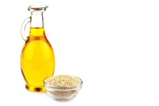 Sesame oil in bottle and sesame seeds stock photo