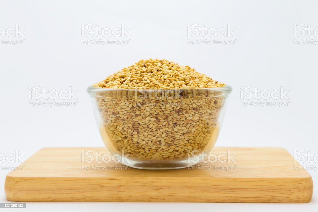 Sesame on glass bolw over wooden board stock photo
