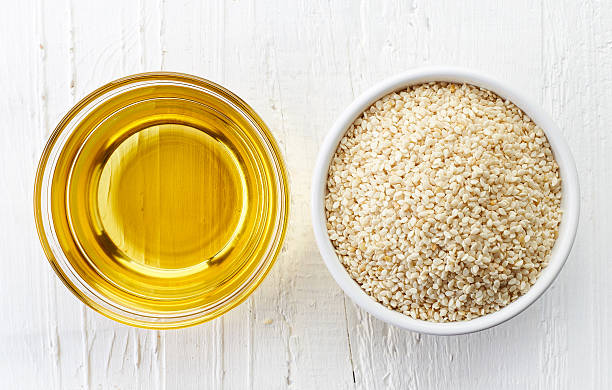 Sesame seed oil and sesame seeds stock photo
