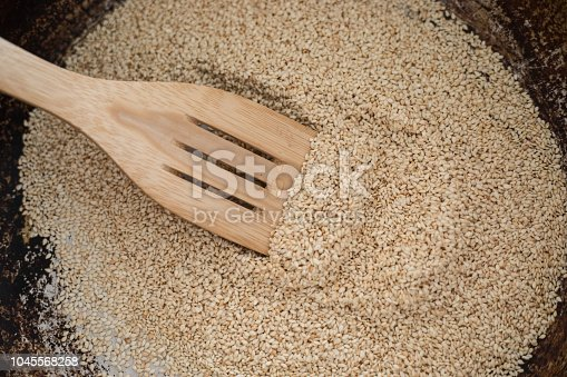 Sesame seed toasted in frying pan, with bamboo laddle. Close-up, high angle vieew, no people