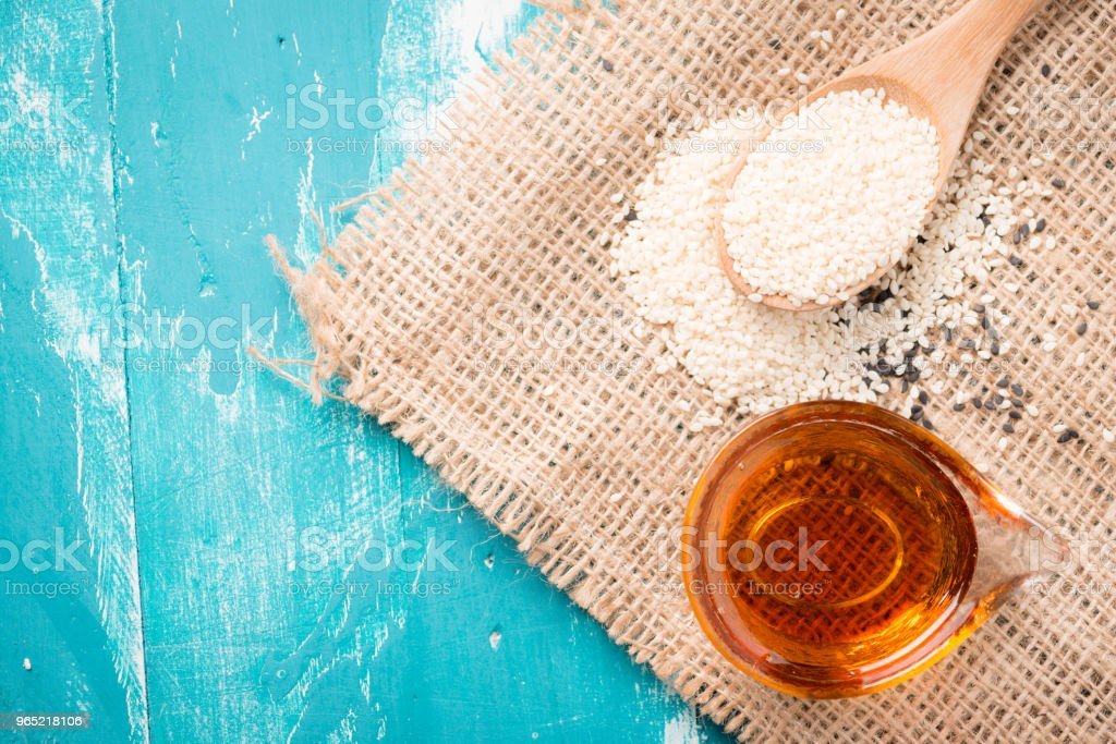 Sesame seeds and sesame oil on a old wooden table royalty-free stock photo