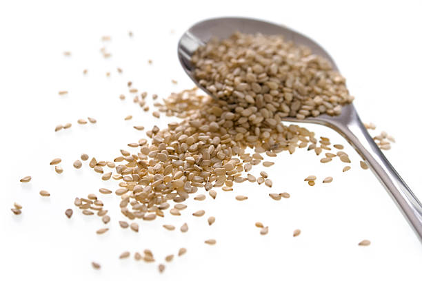 Sesame seeds and small serving spoon stock photo