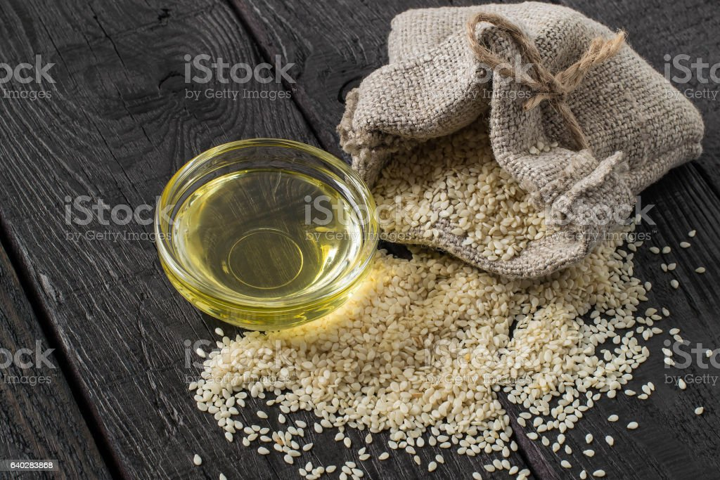 Sesame seeds in a bag and sesame oil in bowl stock photo
