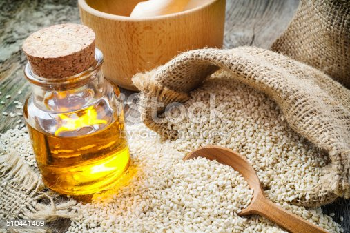 sesame seeds in sack and bottle of oil on wooden rustic table