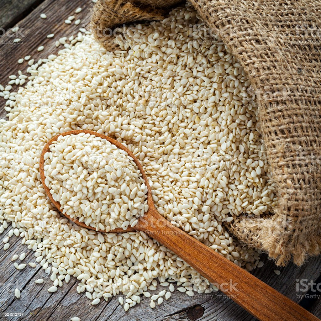 sesame seeds in wooden spoon on wooden rustic table stock photo