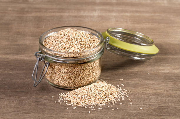 sesame seeds on a wooden background - sesame stock photos and pictures