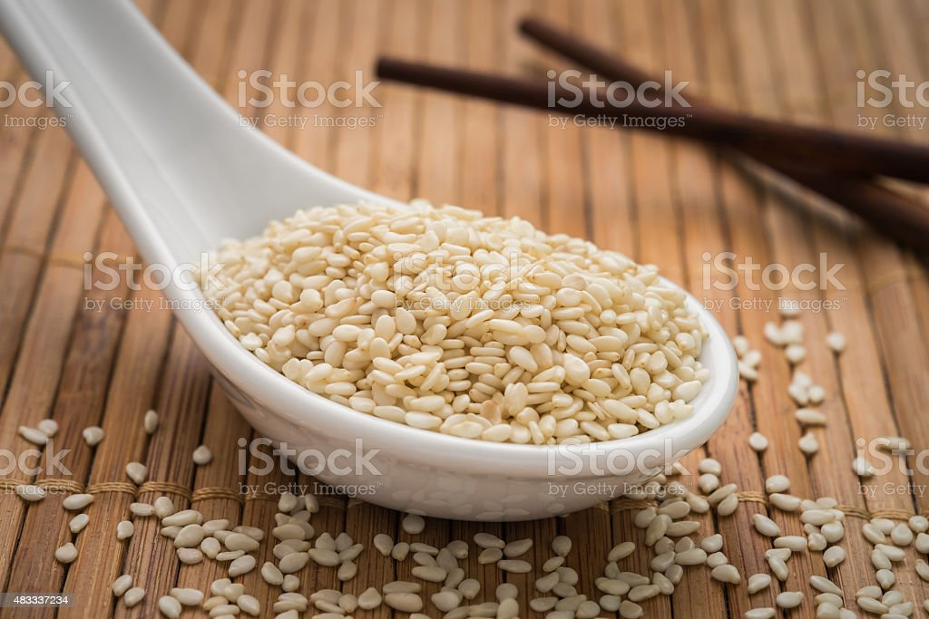 Sesame seeds on spoon stock photo