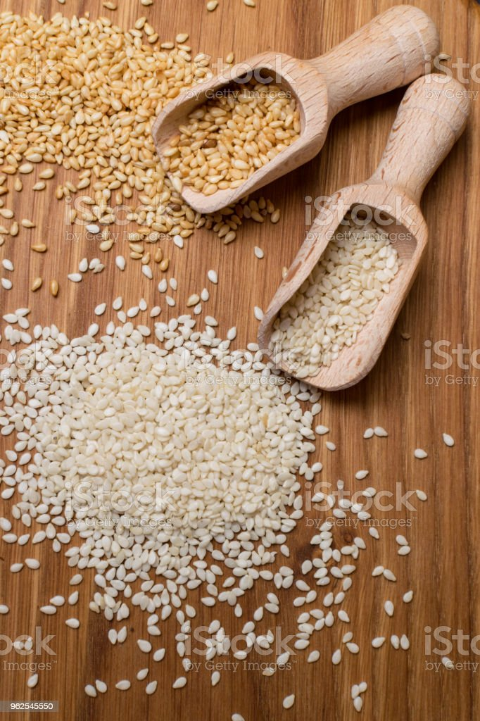 sesame seeds on the wooden background. Two type of sesame seeds in wooden spoon. - Royalty-free Agriculture Stock Photo