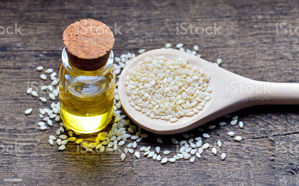 Sesame seeds on wooden spoon and sesame oil. stock photo