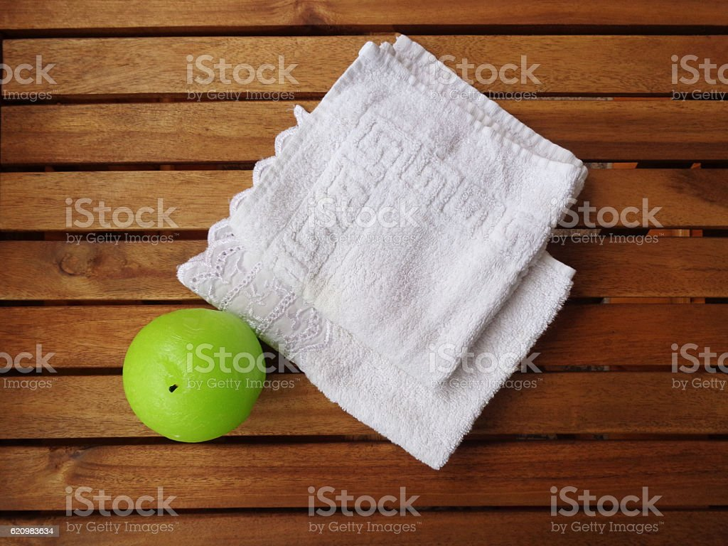 Set bath: Terry white towels and a round green candle foto royalty-free