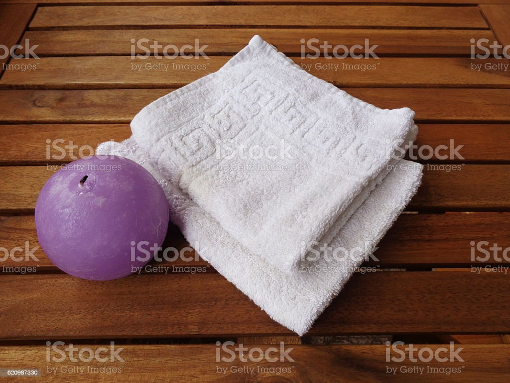 Set bath: Terry white towels and a round purple candle foto royalty-free