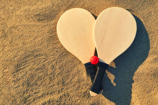 set for a game of beach tennis close-up. wooden rackets and red ball in the sand. basic background for design. - racket stock pictures, royalty-free photos & images