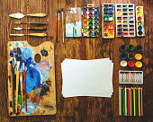 Oil paints, watercolors, brushes and a palette knife for drawing on a wooden background. A few sheets of paper. Colored pencils and pastel on the right. Everything for creativity.