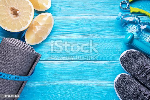 istock Set for sports activities on blue wooden background. Healthy lifestyle concept. Sport equipment, yoga mat, sport shoes, measuring tape, dumbbell, hand expander, sweetie fruit and bottle of water. 912004004
