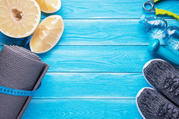 Set for sports activities on blue wooden background. Healthy lifestyle concept. Sport equipment, yoga mat, sport shoes, measuring tape, dumbbell, hand expander, sweetie fruit and bottle of water. stock photo