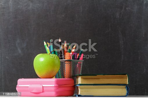 istock Set for the student. A stack of books, an apple, lunch box, pencils against the background of the school black board. The concept of education. Copy space 1158465071