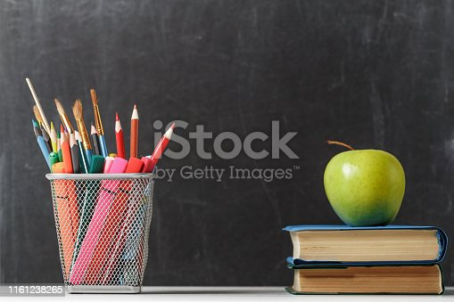 istock Set for the student. A stack of books, an apple, pencils against the background of the school black board. The concept of education. Copy space 1161238265